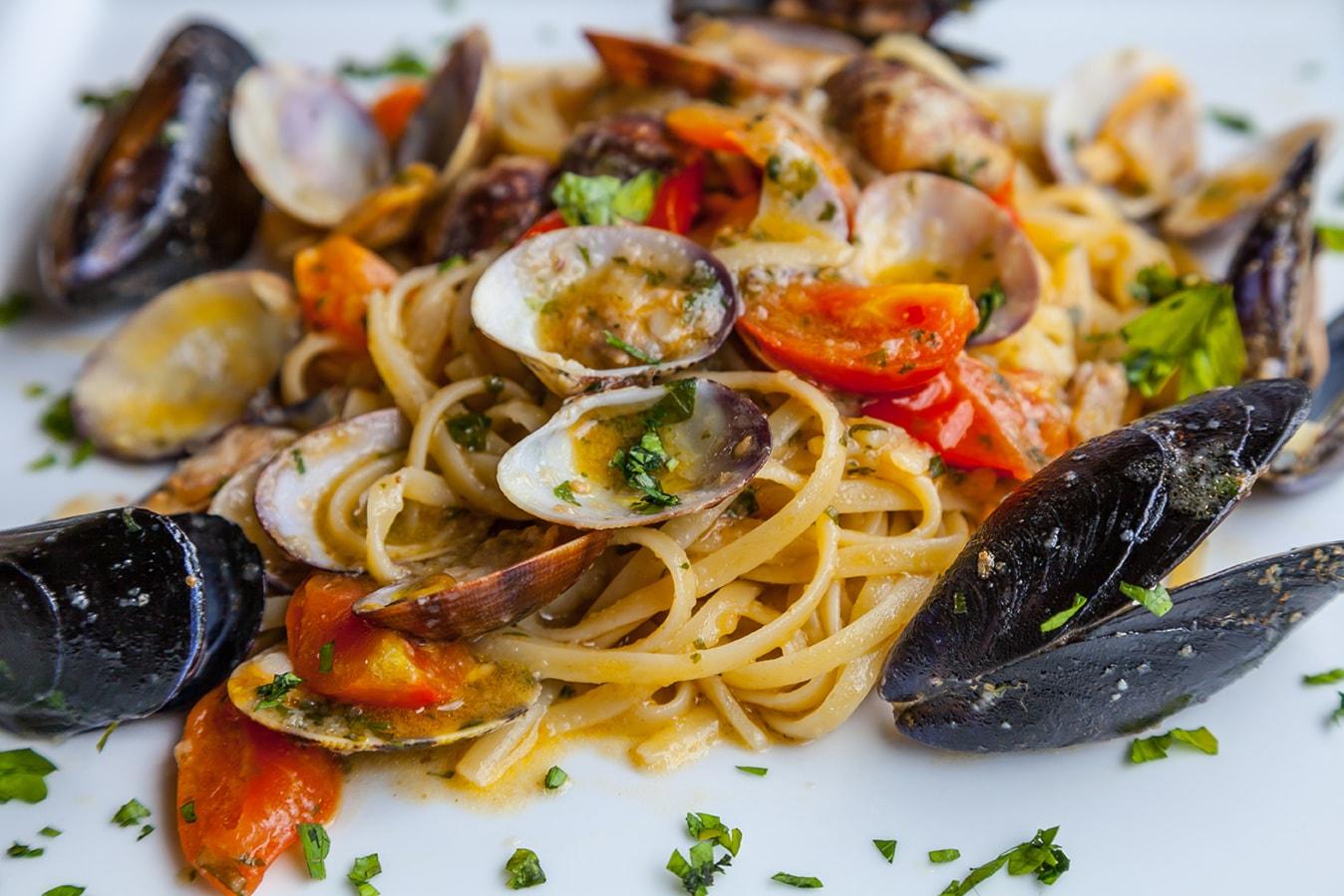 Cena di pesce di coppia con antipasto, scialatielli, frittura, acqua, vino, caffè e sorbetto